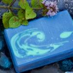 blau-grüne Seife auf Seifenschale mit Minzstängel